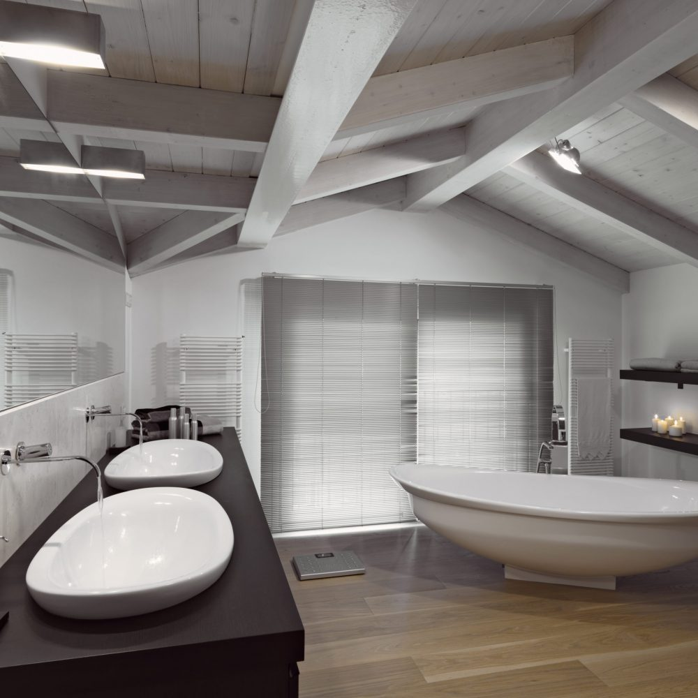 internal shots of a modern bahtroom in the attic room with wooden ceiling and wood floor two counter top on the wooden plan and the bathtub in the center